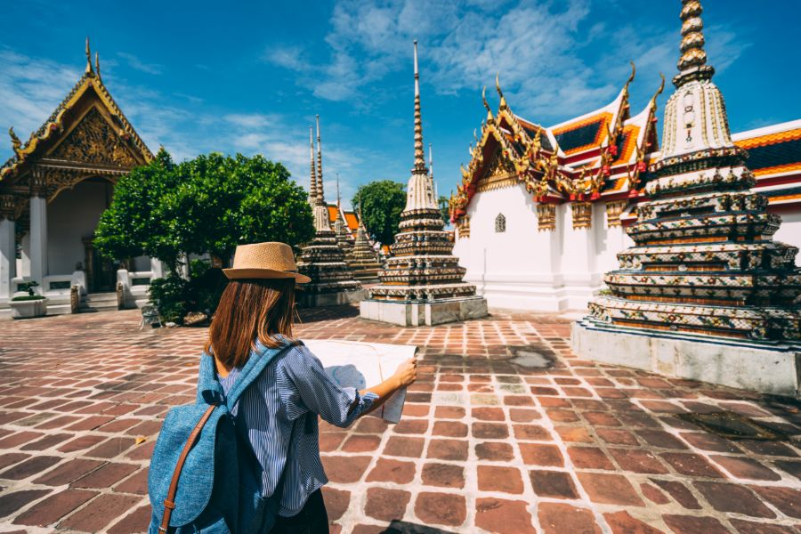 Thailand Bangkok Wat Pho Young woman traveler with backpack and hat looking the map